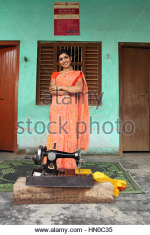 Woman standing with a sewing machine in front of her - Stock Photo