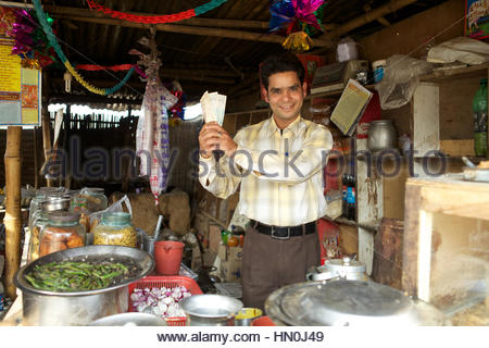 Shopkeeper showing money at a tea stall - Stock Photo