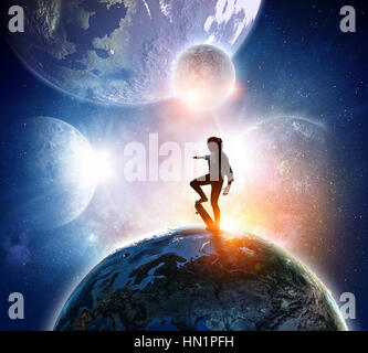 Young woman riding skateboard on Earth palnet. Elements of this image are furnished by NASA - Stock Photo