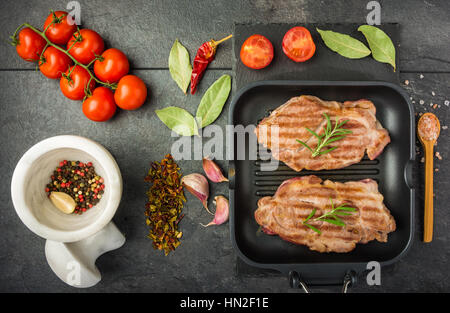 steak with spices and tomatoes cooked on the grill pan on a dark table top view - Stock Photo