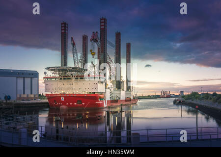 Wind turbine installation vessels in Harbour at sunset. - Stock Photo