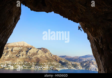 Young man climbing along rocks - Stock Photo