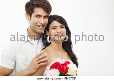 Young man giving bunch of flowers to his wife - Stockfoto