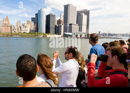 NEW YORK - SEPTEMBER 17 : Tourists on the Staten Island Ferry look out onto Battery park and the Downtown area of - Stock Photo