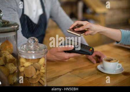 Woman paying bill through smartphone using NFC technology in cafe - Stock Photo