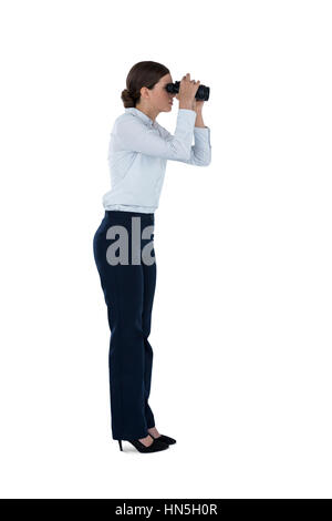 Side view of businesswoman looking through binoculars against a white background - Stock Photo