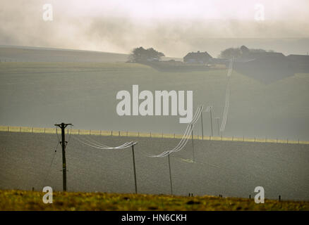 Power lines linking a small remote farm to the national grid, South Downs National park in East Ssussex - Stock Photo