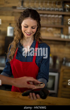 Man paying bill through smartphone using NFC technology in cafe - Stock Photo