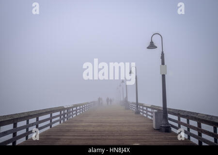 Silhouettes of people in the fog on the Imperial Beach pier. - Stock Photo