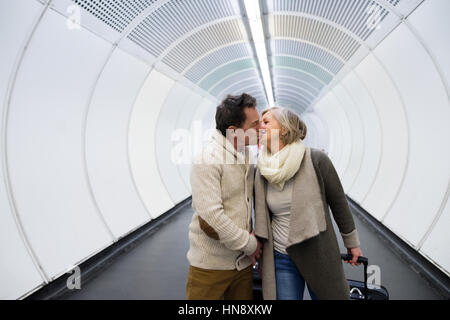 Senior couple in hallway of subway pulling trolley luggage. - Stock Photo