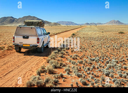 Pickup truck driving on desert road towards the Tiras mountains - Stock Photo