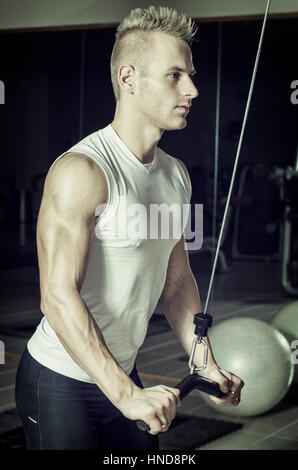 Young handsome man training triceps, on gym equipment, pulling handle on cables - Stock Photo