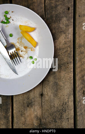 Overhead view of leftovers on a plate with knife and fork on a rustic wooden background - Stock Photo