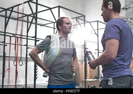 Male friends talking in crossfit gym - Stock Photo