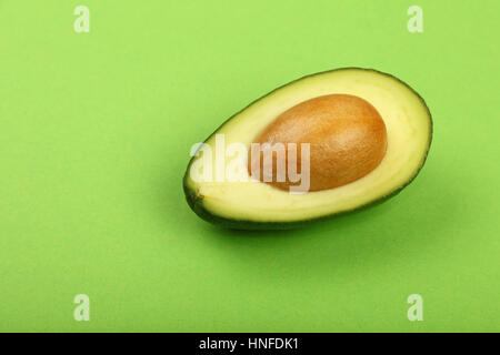 One fresh ripe avocado (Persea gratissima) half with pit stone on green paper background, detail, close up, elevated - Stock Photo