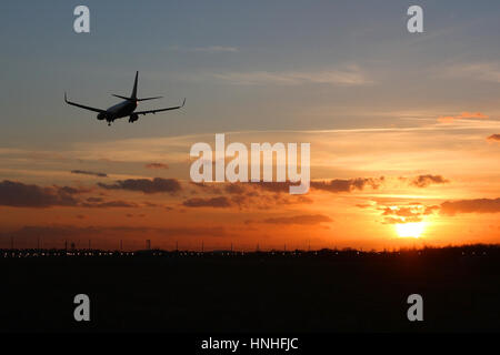 Boeing 737 airliner landing at Stansted Airport on runway 22 as the sun sets. - Stock Photo