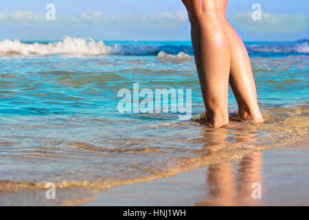 Girl standing with her feet in the water at 7 mile beach in Jamaica - Stock Photo