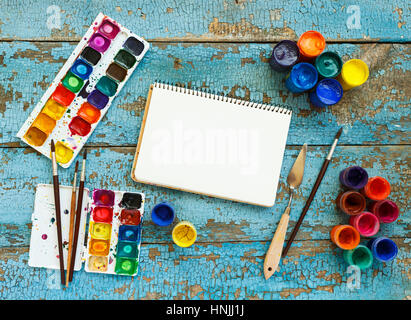 Art of Painting. Painting set: brushes, paints, crayons, watercolor, white paper on a blue wooden background - Stock Photo