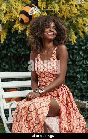 Curly-haired young afro american girl sitting on a wooden white bench. Plant background - Stock Photo