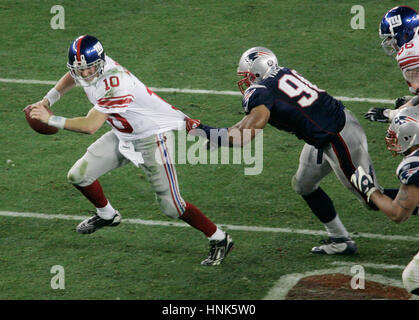 The New York  Giants Eli Manning, left, is grabbed by New England Patriots Rashad Moore in the fourth quarter at - Stock Photo