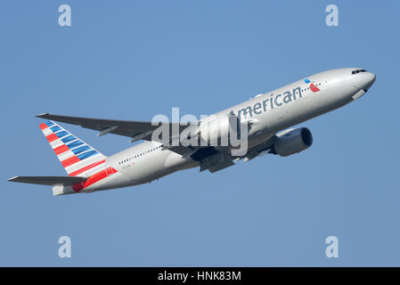 American Airlines Boeing 777-223ER N773AN taking off from London Heathrow Airport in blue sky. Space for copy - Stock Photo
