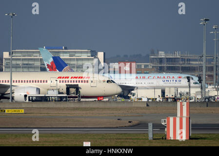 Various airliners on their stands at London Heathrow Airport being loaded for their flights - Stock Photo