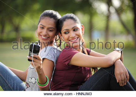 Two friends listening to music on an mp3 player - Stock Photo