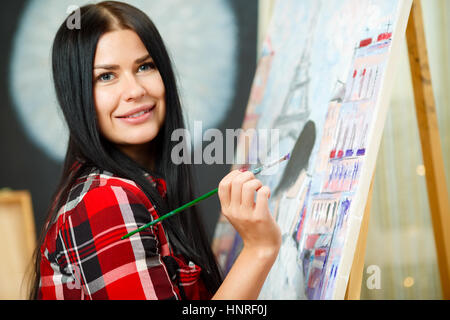 Beautiful long-haired girl with brush near easel which standing on canvas - Stock Photo