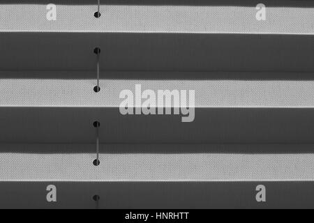 Window gray pleated blind close up with details in home interior. Structure and texture of fabric background. - Stock Photo