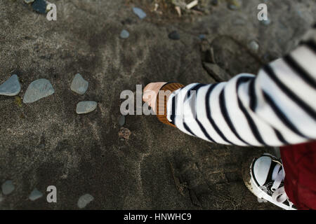 Cropped view of baby boy on beach picking up pebbles - Stock Photo