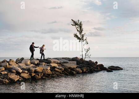 Young couple walking on rocks beside sea - Stock Photo