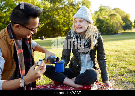 Couple pouring coffee flask on picnic blanket in park - Stock Photo