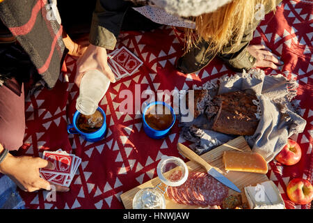Overhead cropped view of couple pouring milk into coffee at  picnic - Stock Photo