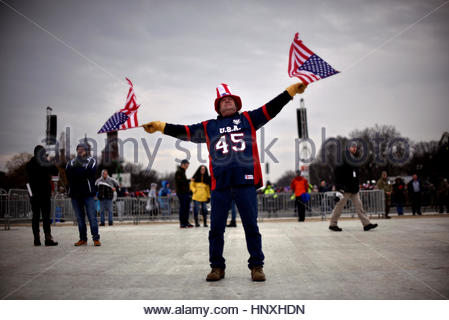 A man at the National Mall waves U.S. flags as U.S. President Donald Trump delivers his inaugural address in Washington, - Stock Photo