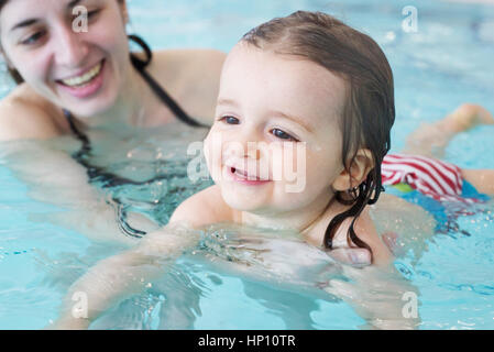Little girl learning to swim with help of parent - Stock Photo