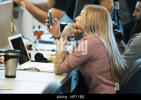 Young woman staring at smartphone in office - Stock Photo