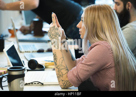 Young woman daydreaming in office - Stock Photo