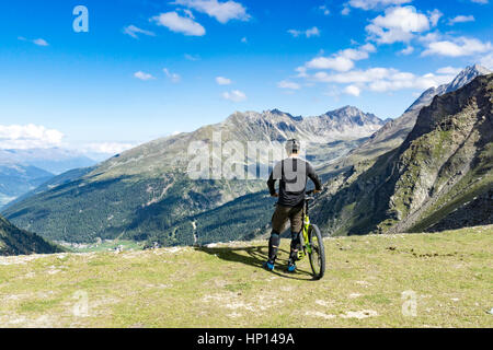 Mountain biker stands on a rim of a summit and enjoys the view of the alps - Stock Photo