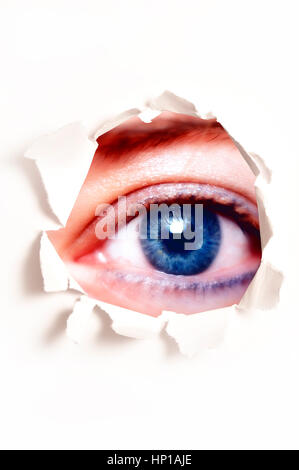 female blue eye behind a hole in a teared white paper - Stock Photo