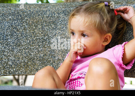 Bored Little Girl Lying On The Wooden Floor With Her Bare