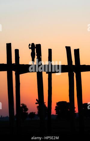 Silhouette of a young woman taking a selfie on U Bein Bridge,, Amarapura, near Mandalay, Myanmar. - Stock Photo