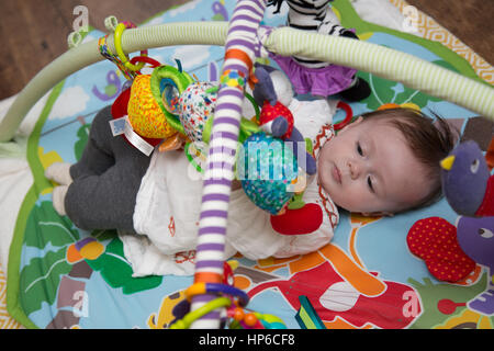 Baby playing on play mat - Stock Photo