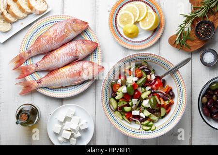 Raw mullet fish, greek salad and other mediterranean ingredients on white wooden table - Stock Photo