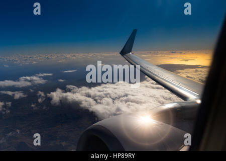View from window of an airplane during sunset or sunrise.Wing view sunset airplane, sunset sky clouds night.Wing - Stock Photo