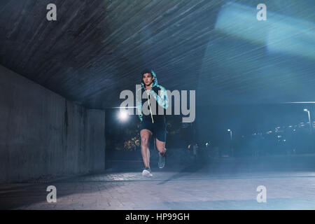 Healthy young man jogging in the city at night. Full length shot of male athlete running under bridge. - Stock Photo