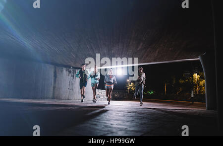 Group of runners running under a bridge in city. Young men and women jogging together at night. - Stock Photo