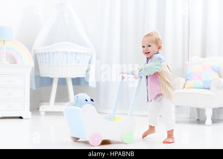 Baby boy learning to walk with wooden push walker in white bedroom with pastel rainbow color toys. Aid toy for child - Stock Photo