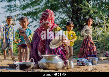 RAJASTHAN, INDIA - NOVEMBER 20, 2016: Rajasthani poor woman cleaning utensils after cooking meal for her family, - Stock Photo
