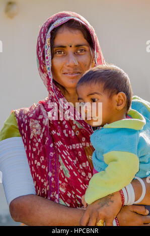 RAJASTHAN, INDIA - NOVEMBER 20, 2016: Unidentified Rajasthani poor woman wearing traditional costume and red sari - Stock Photo