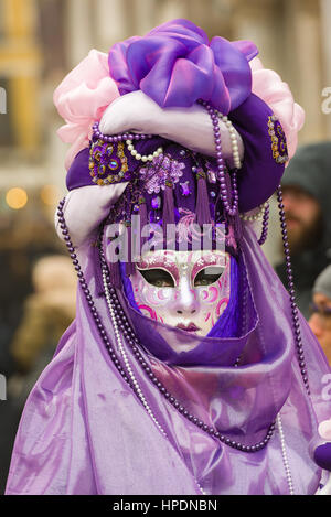 A woman is seen in St Mark's Square wearing a traditional Volto mask during the 2017 Venice Carnival - Stock Photo